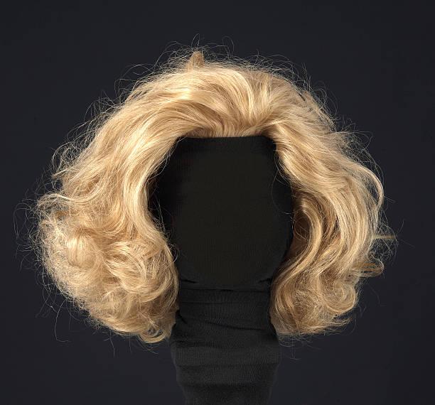 blonde wig isolated on black background - blond curly hair stockfoto's en -beelden