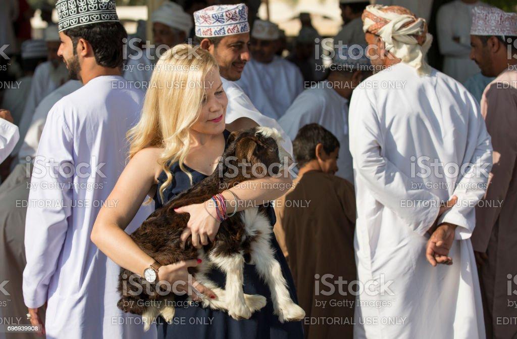 Blonde with a baby goat at Nizwa Habta market stock photo