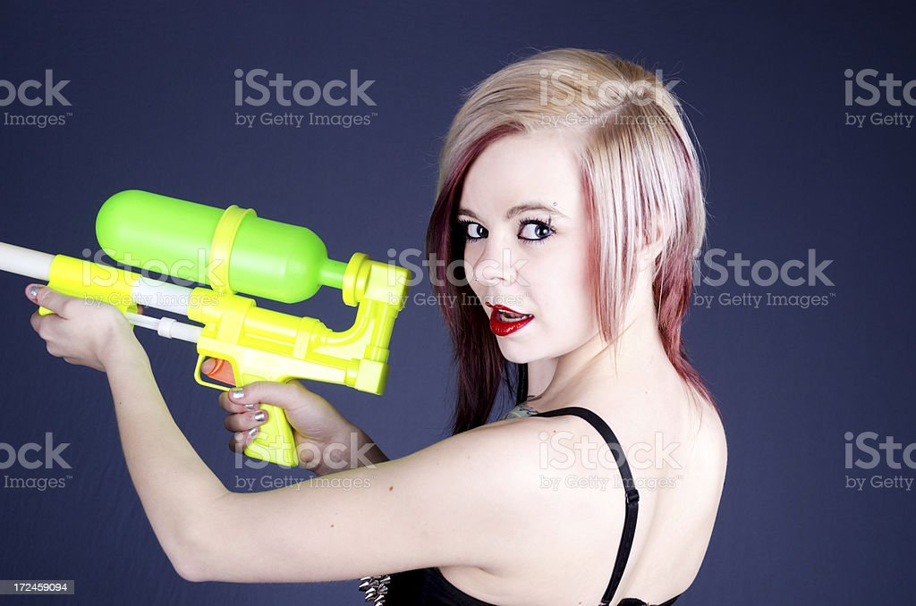 Blonde with colourful water gun talking over shoulder. royalty-free stock photo