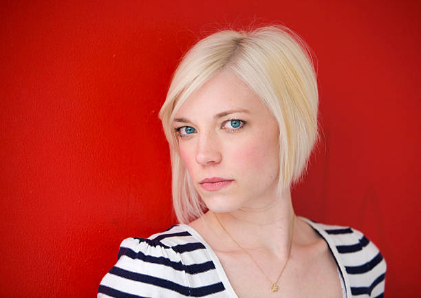 donna bionda in rosso - capelli ossigenati foto e immagini stock