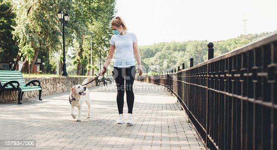 Blonde woman and her dog walking in the park while wearing a medical mask on face during the coronavirus