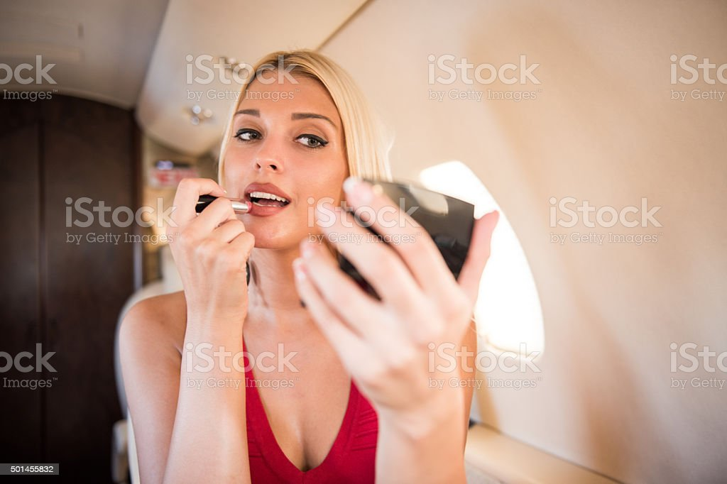 Blonde woman applying lipstick stock photo
