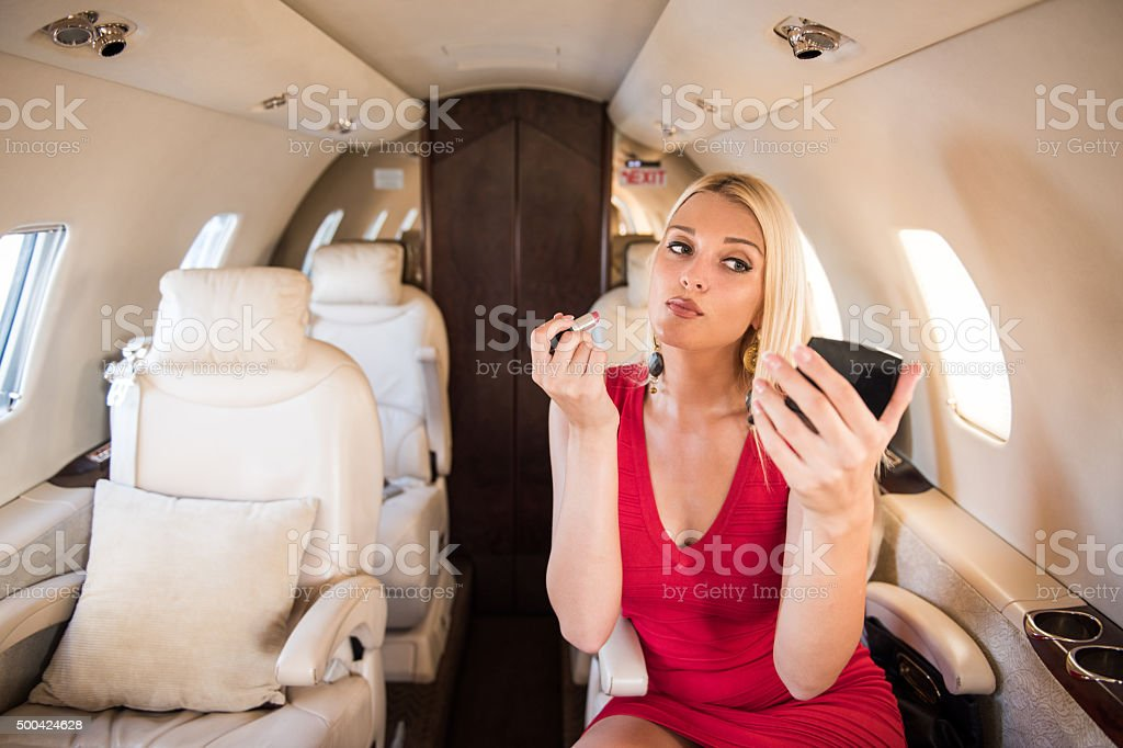 Blonde woman applying makeup in private jet airplane stock photo
