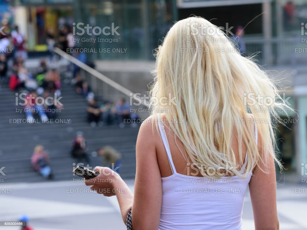 Blonde woman approaching Sergels torg stairs, famous landmark and meeting point stock photo