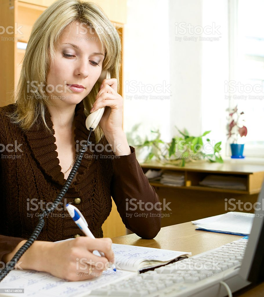 A blonde woman at work on the phone taking notes stock photo