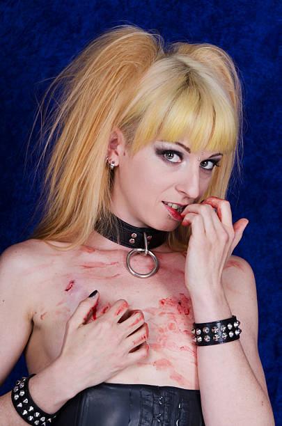 blonde frau beißen nägel, spielt mit blut auf der brust. - armband i gummi stock-fotos und bilder