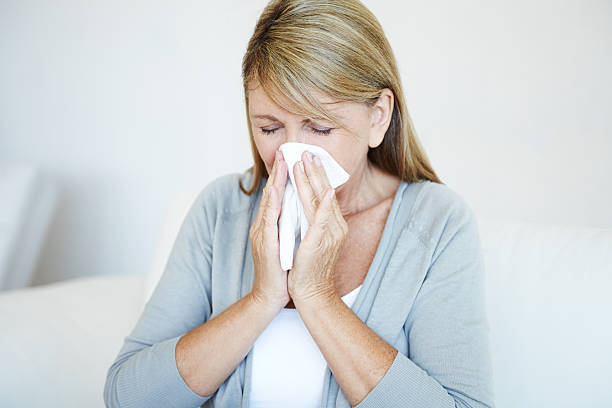 Blonde woman blows nose into tissue stock photo