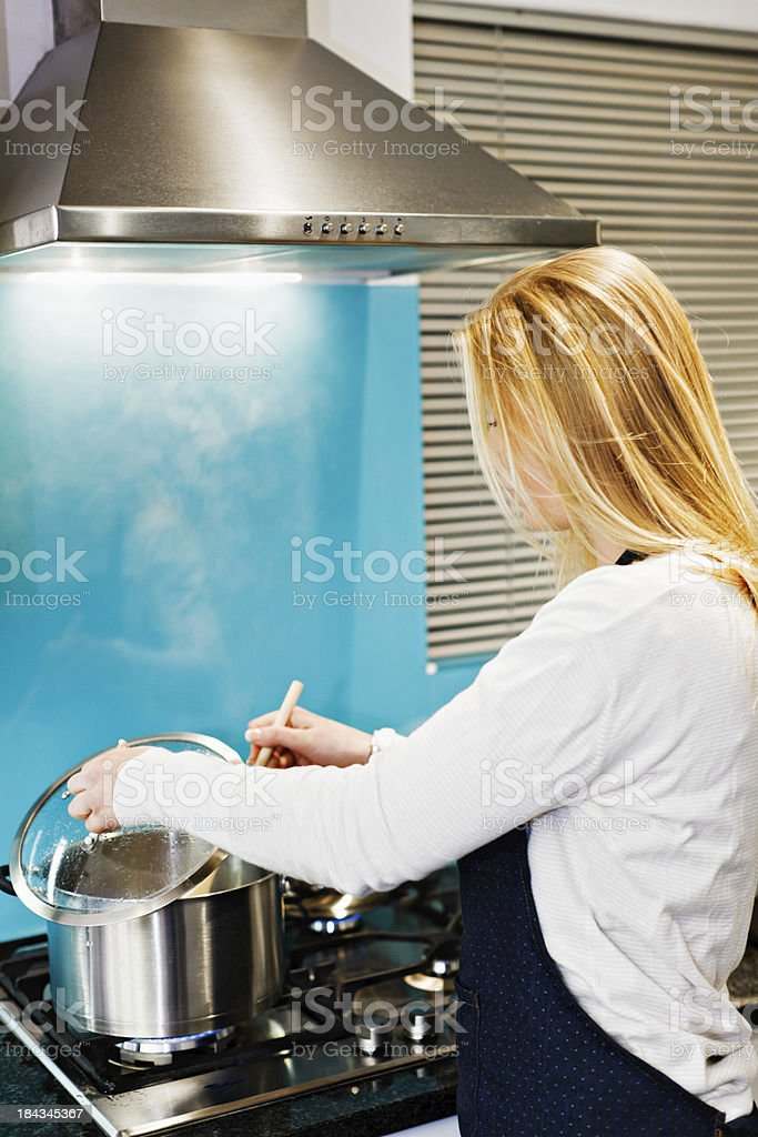 Blonde woman checks steaming contents of pan cooking on stove stock photo