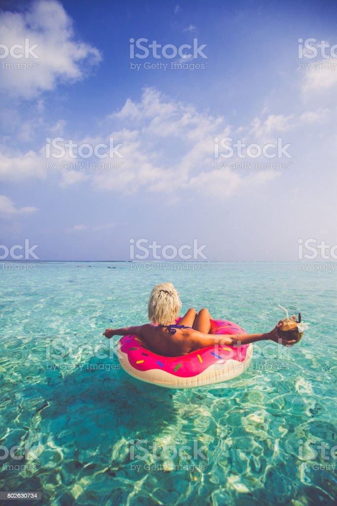 Blonde woman chilling and floating on inflatable doughnut in ocean, Maldives stock photo