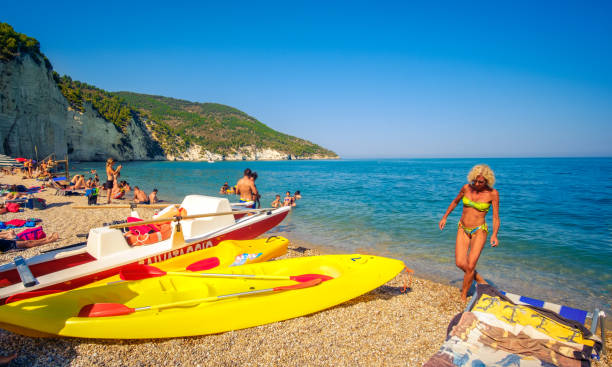 blonde woman come out of the sea water in the Vignanotica beach, one of the top beaches in Gargano - Italy stock photo