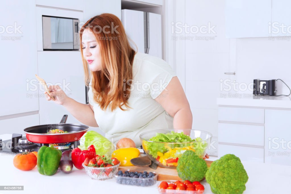 Blonde woman cooking vegetables stock photo
