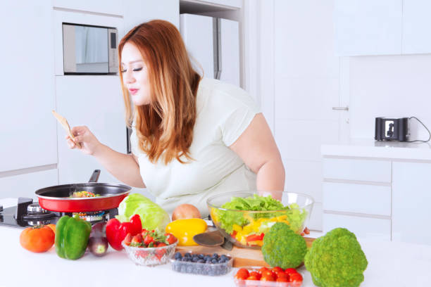 blonde frau kocht gemüse - fett nährstoff stock-fotos und bilder