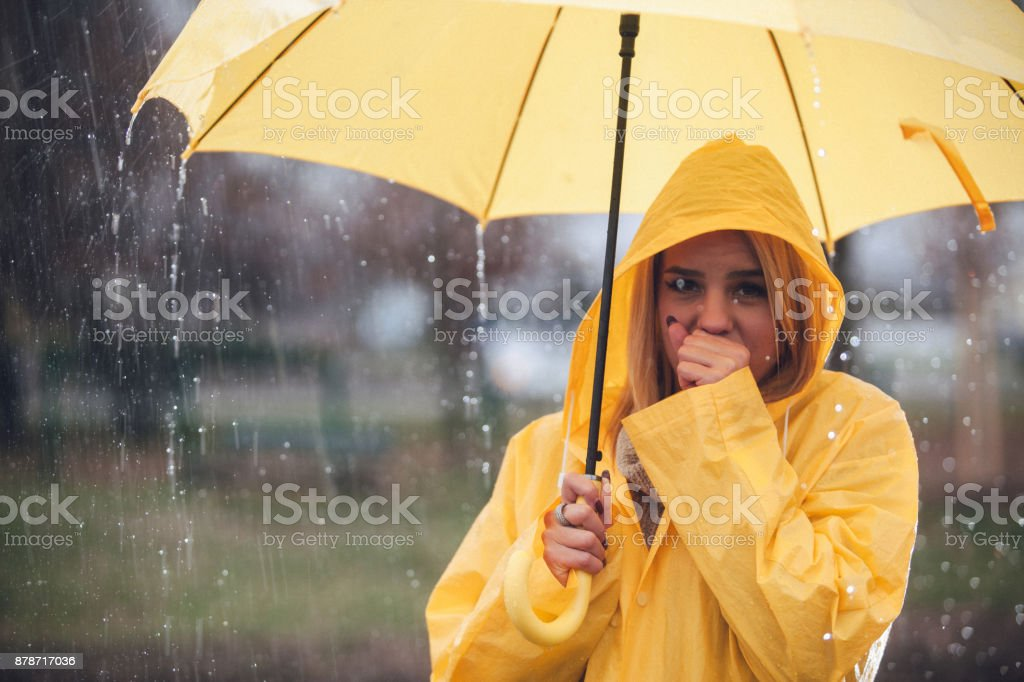 Blonde woman cough on rain and holding umbrella stock photo