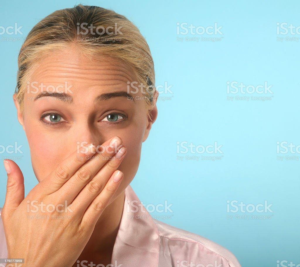 Blonde woman covering nose with hand while sneezing stock photo