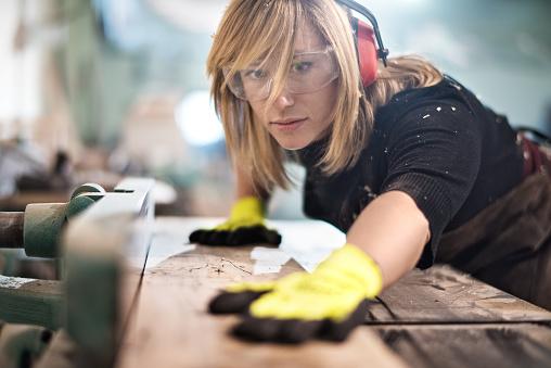 Blonde woman cutting a plank