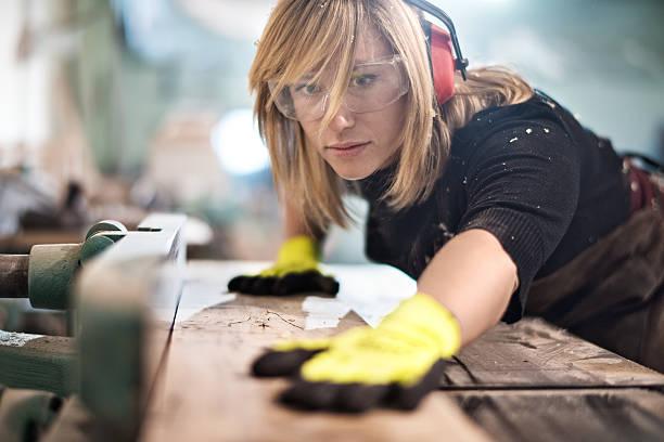 blondine frau schneiden ein plank - schreiner stock-fotos und bilder