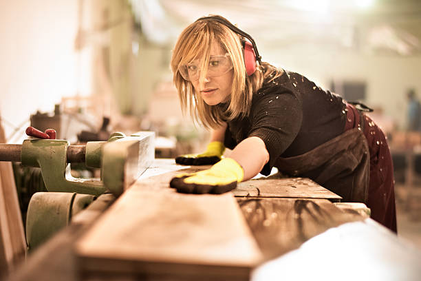 Blonde woman cutting planks Female craftperson with protective equipment working with planks in workshop. She is making furniture parts. carving craft product stock pictures, royalty-free photos & images