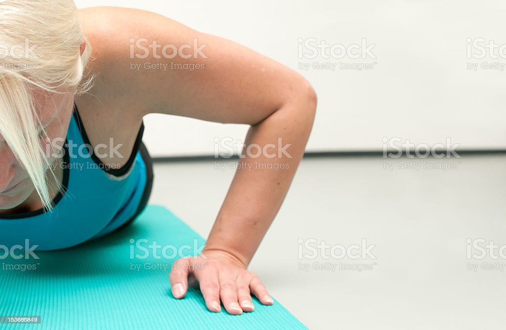 Blonde woman doing push ups at the gym stock photo