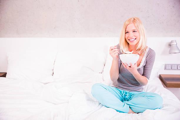blonde frau essen frühstück im bett - quarkspeise stock-fotos und bilder