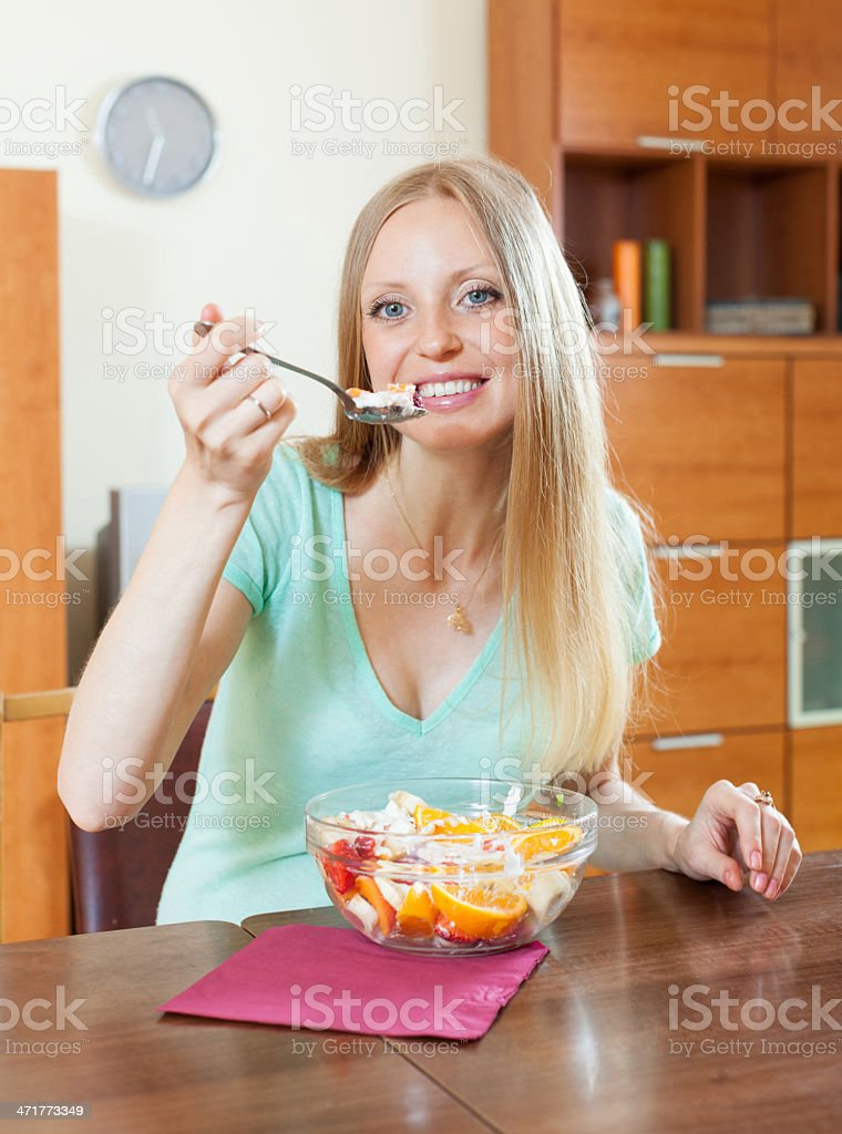 blonde woman eating  fruit salad at home royalty-free stock photo