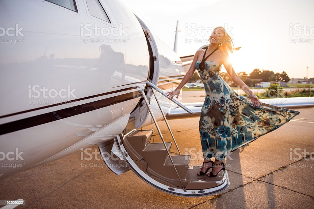 Blonde woman entering private airplane stock photo