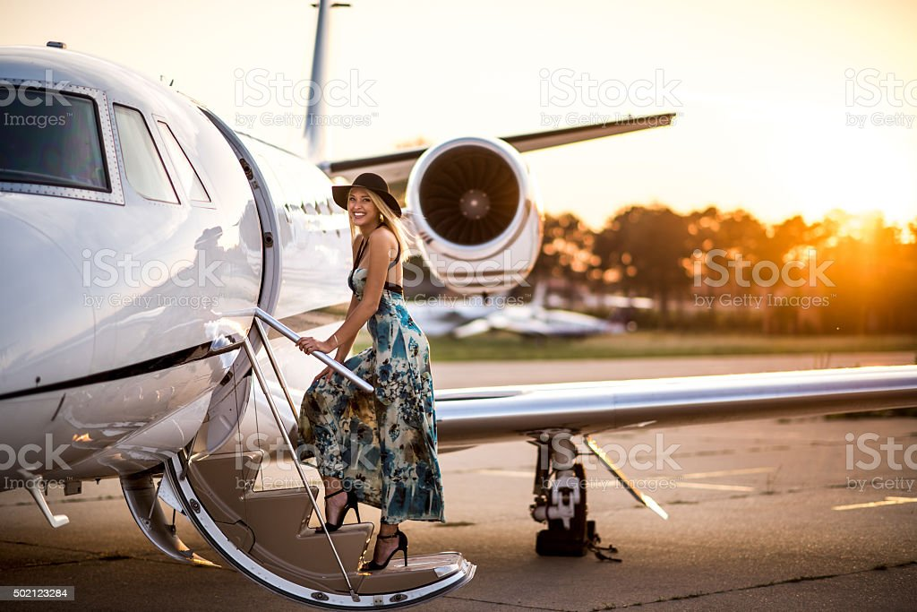Blonde woman entering private jet airplane stock photo