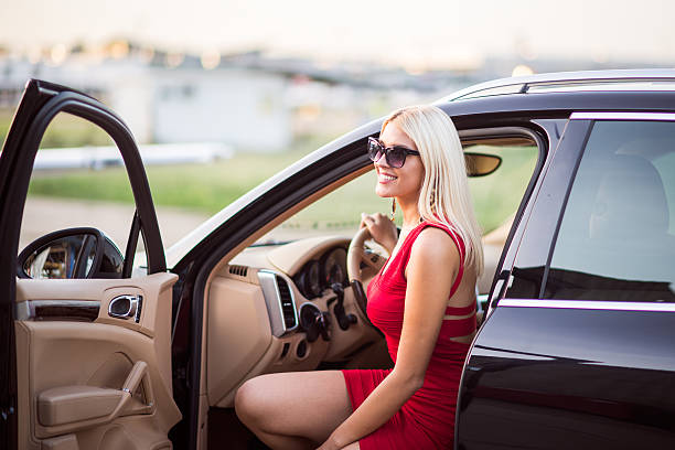 Blonde woman exiting the black car stock photo