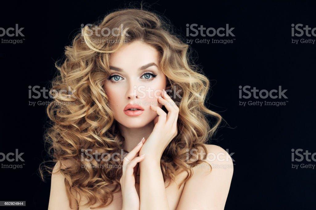 Blonde woman fashion model posing against black background stock photo