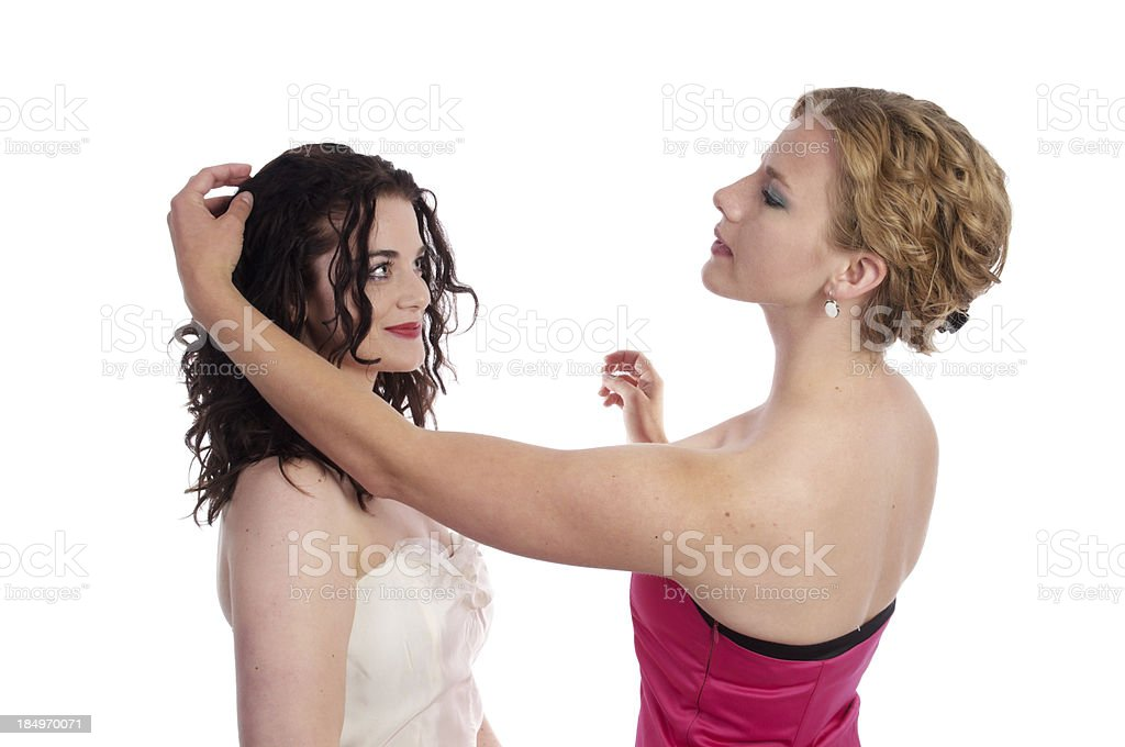 Blonde woman fixing dark haired sister stock photo