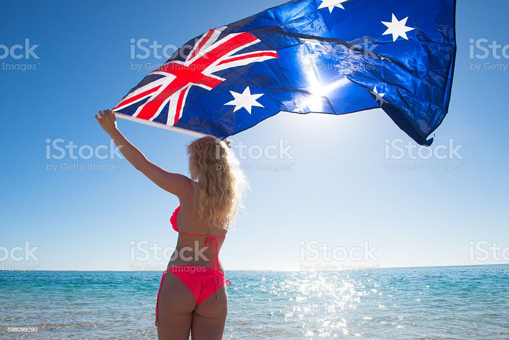 Blonde woman flying Australian flag at beach stock photo