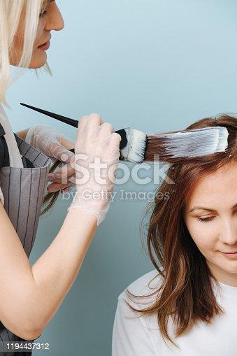 istock Blonde woman hairdresser applying developer on client's hair over blue. 1194437312