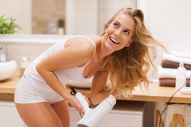 blonde frau hat spaß beim trocknen haar im bad - feminine badezimmer stock-fotos und bilder