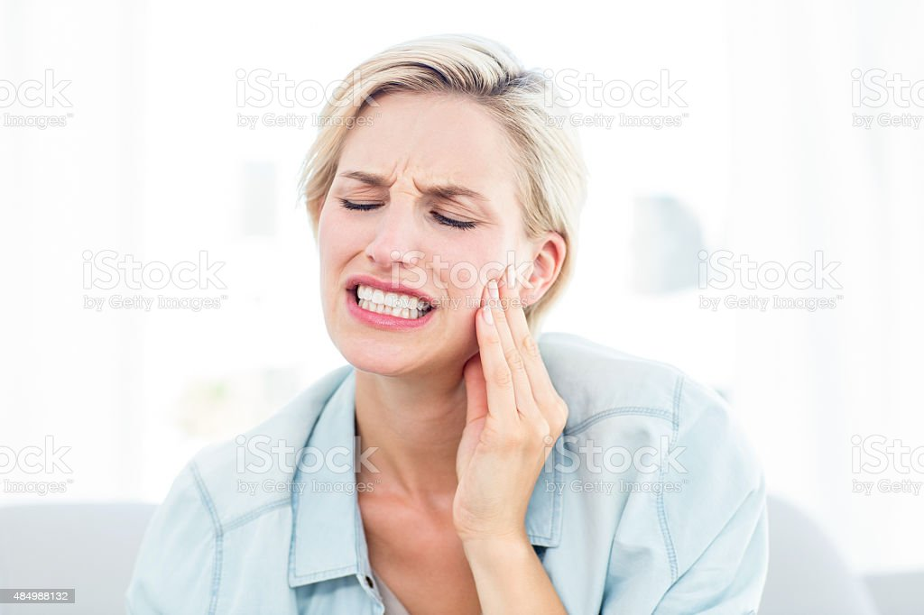 Blonde woman having toothache stock photo