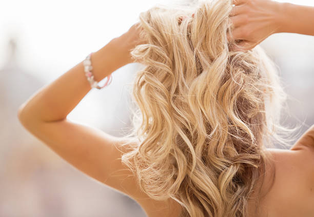 blonde woman holding her hands in hair - human hair stock photos and pictures