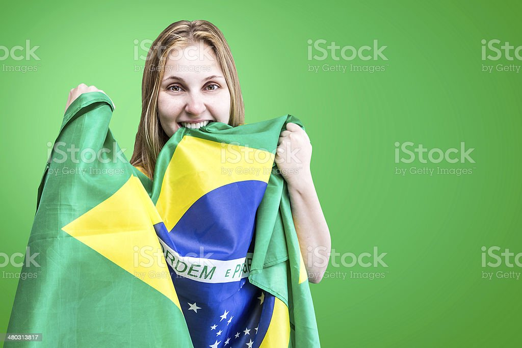 Blonde Woman holds the flag of Brazil on green background stock photo