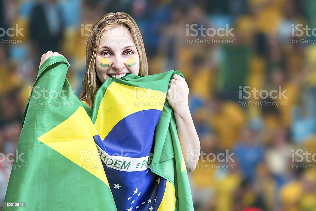 Blonde Woman holds the flag of Brazil on Stadium stock photo