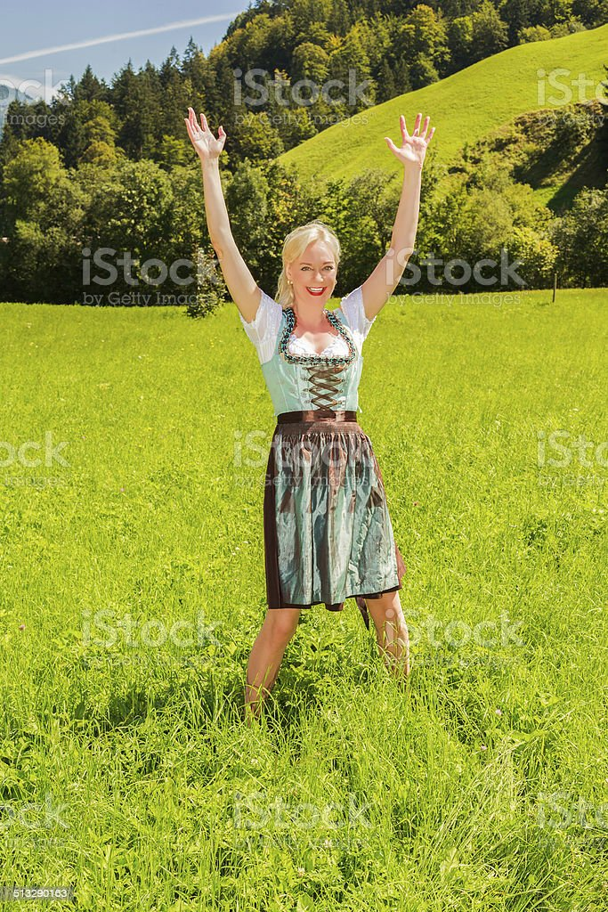 Blonde woman in a dirndl is happy in a green meadow stock photo