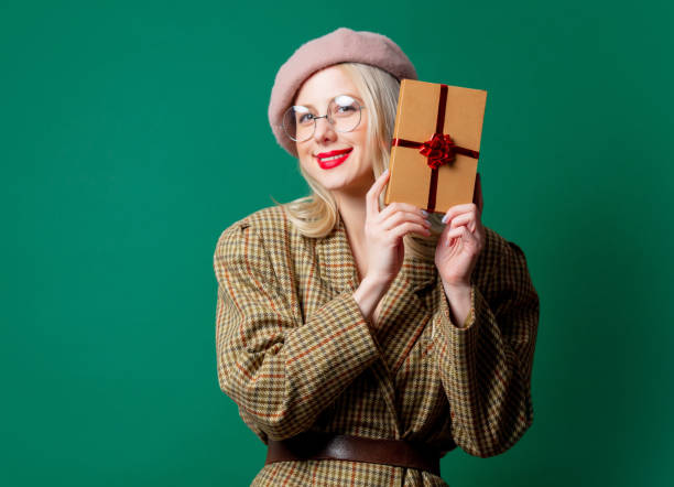 Blonde woman in British style jacket with gift box stock photo