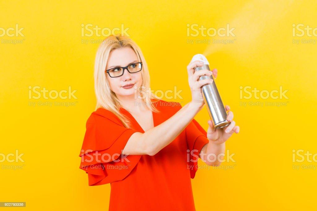 Mulher loira de vestido com pulverizador - foto de acervo