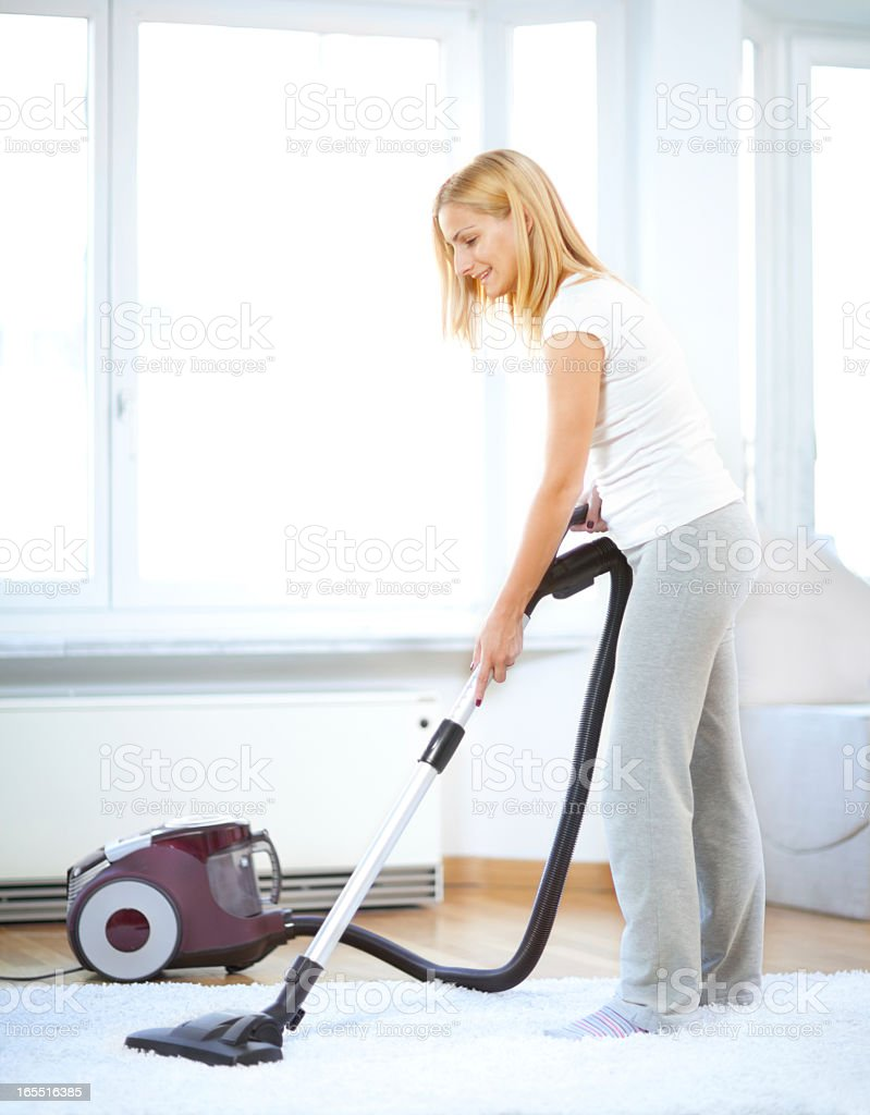 Blonde woman in lounge clothes vacuum-cleaning her home stock photo