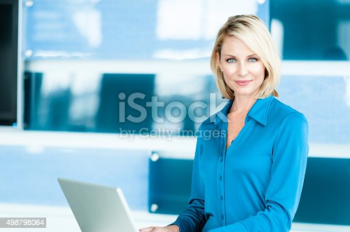 Thirty-something blonde female woman working on laptop computer in modern interior