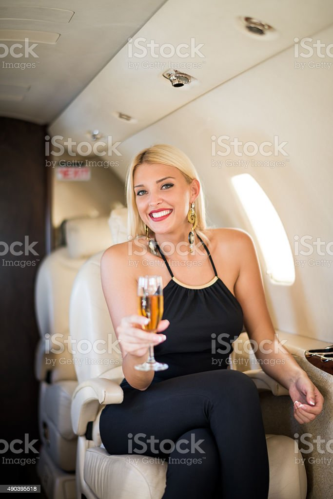 Blonde woman in private jet airplane stock photo