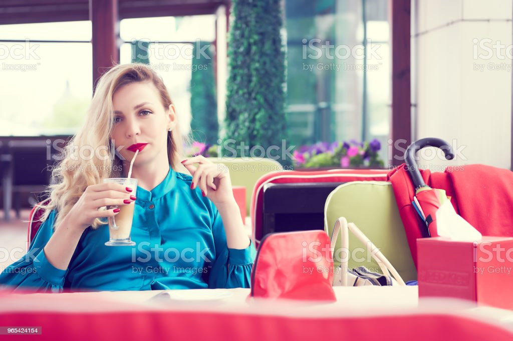 Blonde woman in the blue dress sitting at the cafe and drinking milk cocktail. Beauty portrait royalty-free stock photo