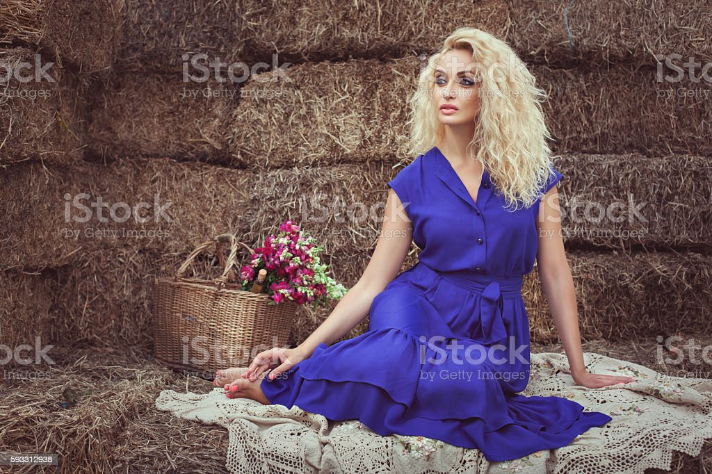 Blonde woman in the hayloft. stock photo
