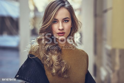 istock Blonde woman in urban background. 641678418