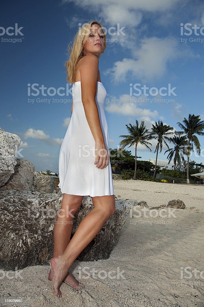 Blonde Woman in White Dress on Sunny Beach, Looking Down royalty-free stock photo
