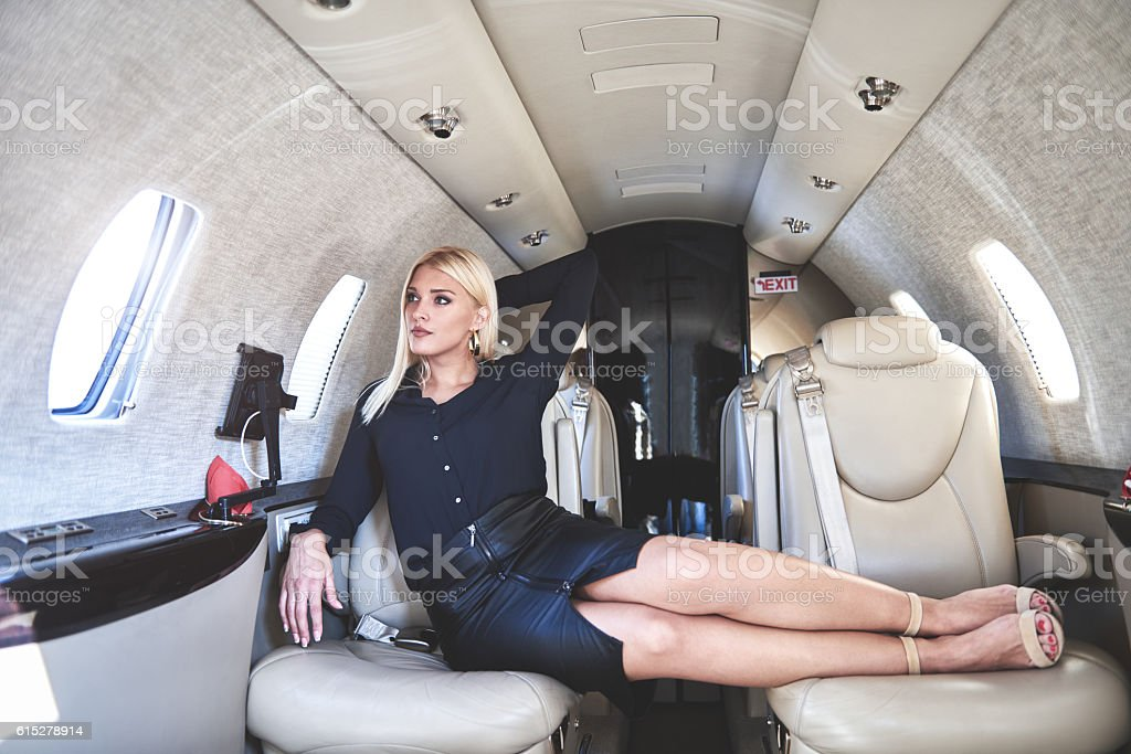 Blonde woman inside private jet aeroplane stock photo