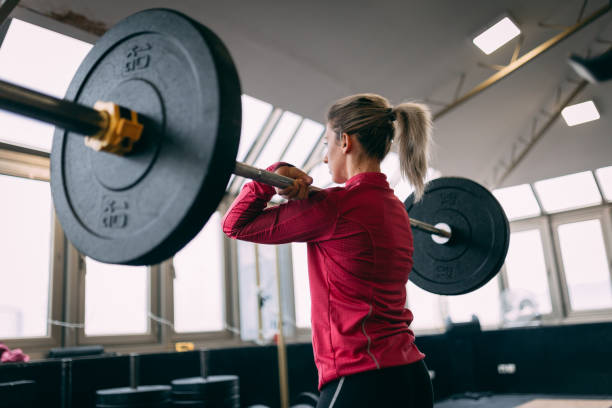 Blonde woman is doing squats with weight at the gym stock photo