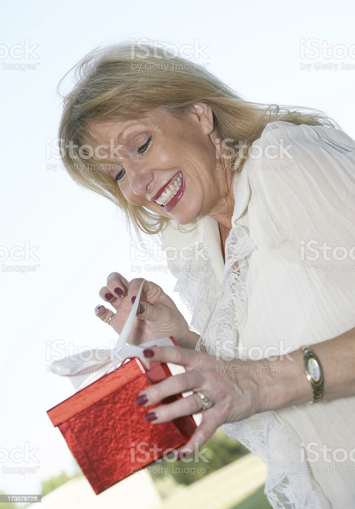 Blonde Woman Is Excited About Opening Her Gift Box royalty-free stock photo