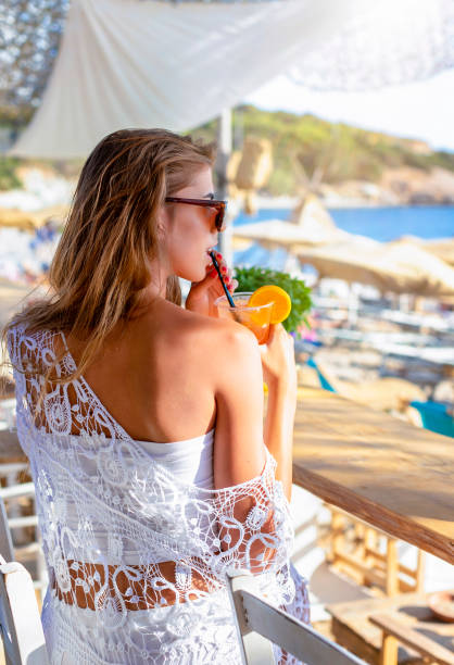 Blonde woman is having a cocktail at a beach bar during summer time - foto stock